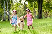 Two young girls running with golden retriever in park