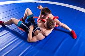 Two Young Man  Wrestlers In Red And Blue Uniform Wrestling  On A Blue Wrestling Carpet In The Gym. G poster