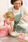 stock photo of grandmother  - Grandmother and granddaughter baking cookies prepare dough - JPG