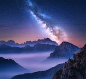 Milky Way Over Mountains In Fog At Night In Summer. Landscape With Alpine Mountain Valley, Purple Lo poster