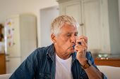 Senior man using asthma inhaler for relief an attack at home for preventing attack. Old man using me poster
