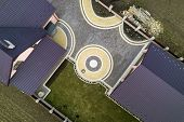 Aerial Top View Of House Shingle Roof On Background Of Green Lawn And Colorful Paved Yard With Geome poster