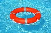 Orange Lifebuoy Pool Ring Float On Blue Water. Life Ring Floating On Top Of Sunny Blue Water. Life R poster