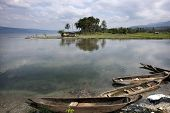 Fishing boats and calm waters reflection the skies at lake Singkarak, the largest tectonic lake in S