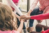 Multiethnic Women Wearing Pink Color Clothes Put Their Hands Together In Stack Empowering Each Other poster