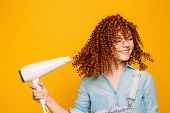 Curly Red-haired Woman Using Hair Dryer On Yellow Background. Making Perfect Curls poster