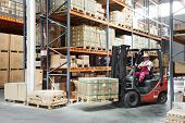 warehouse worker driver in uniform delivery and loading cardboxes by forklift stacker loader