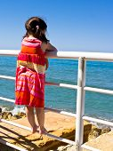 Young girl looking out to sea