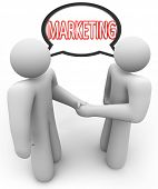 Two people networking and shaking hands with the word Marketing in a speech bubble above their heads