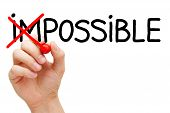 stock photo of impossible  - Hand turning the word Impossible into Possible with red marker isolated on white - JPG