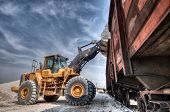 pic of backhoe  - Wheel loader excavator with backhoe unloading clay - JPG
