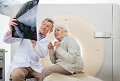 Mature male radiologist explaining CT Scan to an elderly female patient