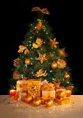 Image of gifts under beautiful Christmas tree isolated on black background, green fir tree decorated