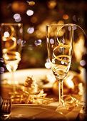 Picture of Christmas table setting, retro style photo, glasses for champagne, golden Christmastime d