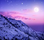 Photo of beautiful snowy mountains on purple sunset background, Faraya mountain in Lebanon covered w