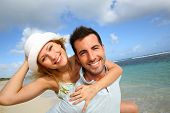 stock photo of piggyback ride  - Cheerful couple enjoying vacation at the beach - JPG