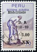 PERU - CIRCA 1969: A stamp printed in Peru dedicated to agrarian reform shows a farmer punching a ho