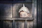 Boy in a tin foil hat peeking out of a window