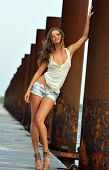 Beautiful sexy woman posing in jeans shorts at rusty boat marina