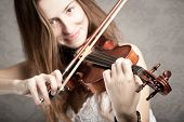 young woman playing violin on gray background