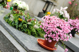 stock photo of urn funeral  - Funeral flowers placed on the grave at All souls holiday - JPG