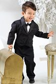 Portrait of a little boy in black tuxedo with old case