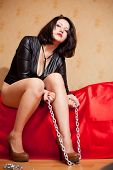 foto of sado-masochism  - beautiful young woman sitting on a couch and holding a chain - JPG