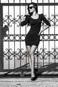 stock photo of tight dress  - young woman in tight dress lean on wrought iron fence full body shot bw - JPG