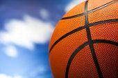 Basketball ball over blue sky background