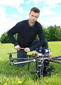 Portrait of confident young technician fixing propeller of UAV octocopter in park