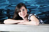 A beautiful teen girl leaning on a balustrade with a watery background.