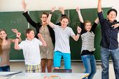 stock photo of middle class  - Successful Teacher and students jump in front of a blackboard with math work in a classroom or class school while lesson - JPG