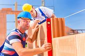 stock photo of bricklayer  - Construction site workers or bricklayer with helmets controlling building walls with a bubble level - JPG