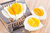 Egg Cutter And Cutted Eggs On Wooden Table