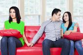 image of cheating  - Beautiful young woman holding hands with man sitting near his girlfriend at home - JPG