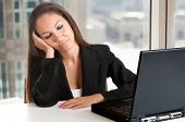 stock photo of sleepy  - Businesswoman sitting at her desk tired and sleepy in an office - JPG