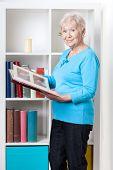 Elderly Woman Looking Through Photo Album