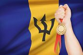 Medal In Hand With Flag On Background - Barbados