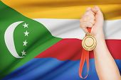 Medal In Hand With Flag On Background - Union Of The Comoros
