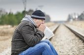 Worried man breathe into a paper bag on a railway