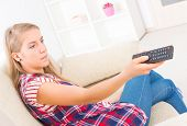 Bored young woman holding remote control and watching tv at home
