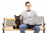 Young man sitting on a bench with his dog and working on laptop isolated on white background
