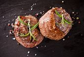 stock photo of wood pieces  - Pieces of red meat steaks with rosemary served on black stone surface - JPG