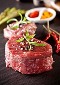 Pieces of red raw meat steaks with rosemary served on black stone surface.