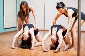 image of pole dance  - Cute pole dancing students working on their flexibility with the help of a couple of instructors