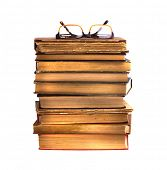 Pile of ancient books and glasses, isolated on white background.