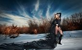 Lovely young lady posing dramatically with long black veil in winter scenery. Gothic blonde woman