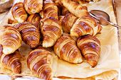 stock photo of tong  - Fresh homemade french croissants served for breakfast with pair of tongs - JPG