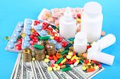 Prescription drugs on money background representing rising health care costs. On color background