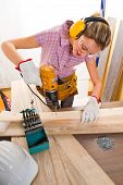 picture of hand drill  - Female carpenter at work using hand drilling machine - JPG